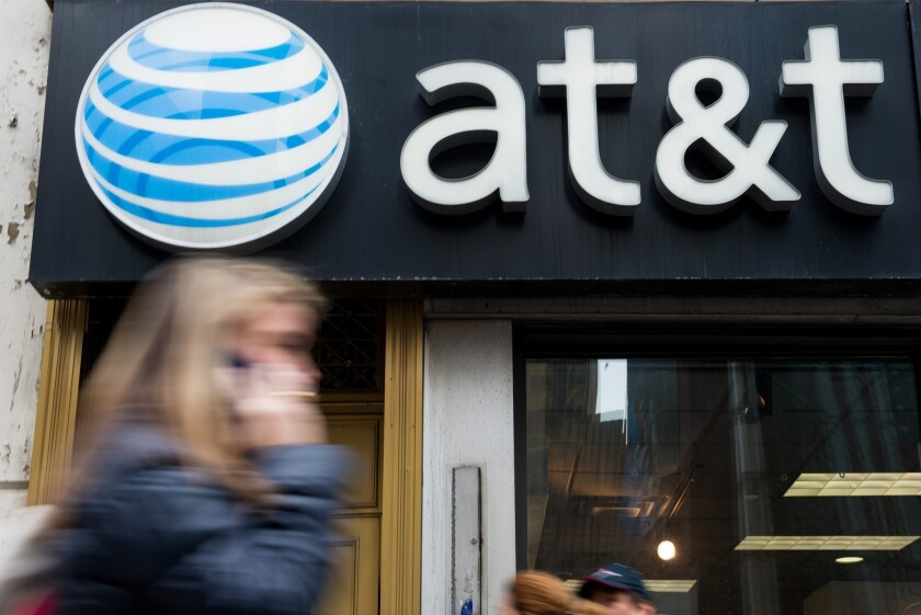 A woman talks on a cellphone while walking past an AT&T Inc. store in New York City in January.