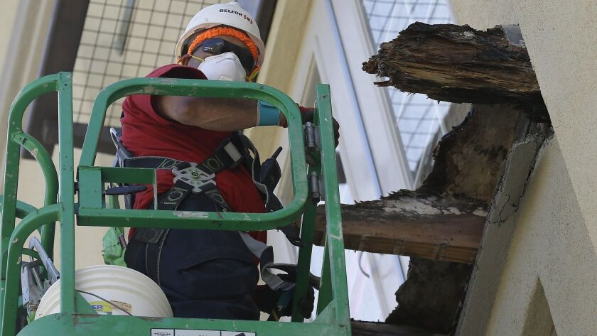 A crew work on the remaining wood of an apartment building balcony that collapsed in Berkeley, Calif., Thursday, June 18, 2015. A balcony broke loose from an apartment building during a 21st birthday party early Tuesday, killing several.