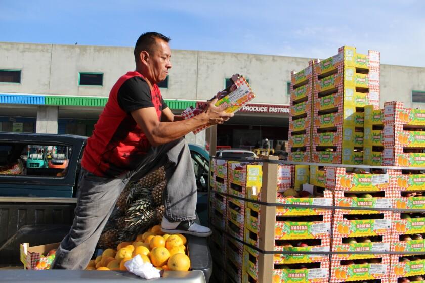 José López acomoda cajas de mangos y naranjas en su vehículo, después de comprar en la Central de Abastos de Los Ángeles.