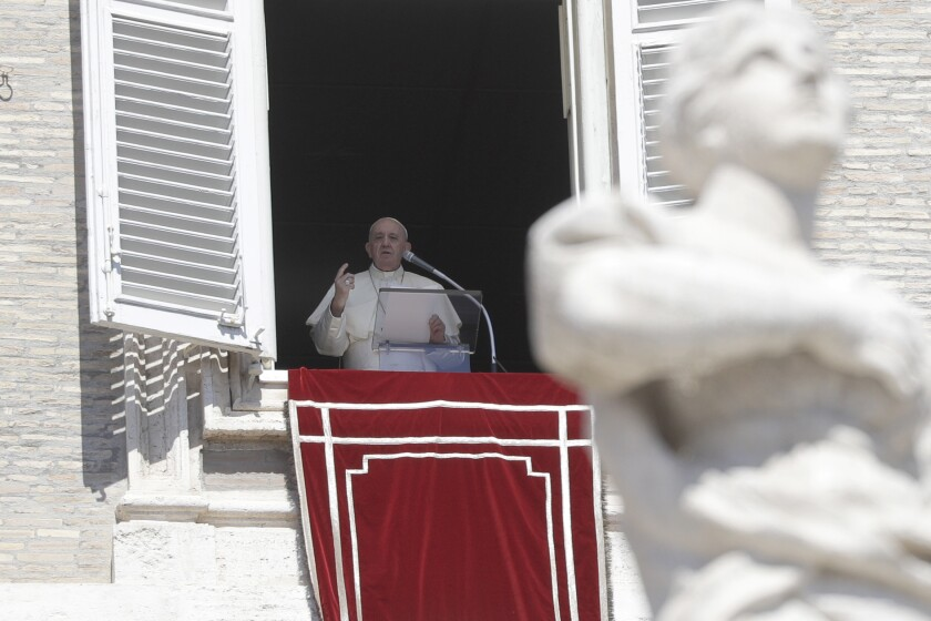 Pope Francis recites the Angelus noon prayer from his studio window overlooking St. Peter's Square.
