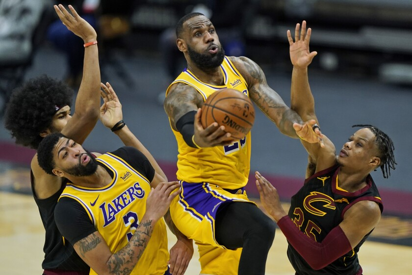 Lakers' LeBron James drives to the basket against Cleveland Cavaliers' Isaac Okoro.