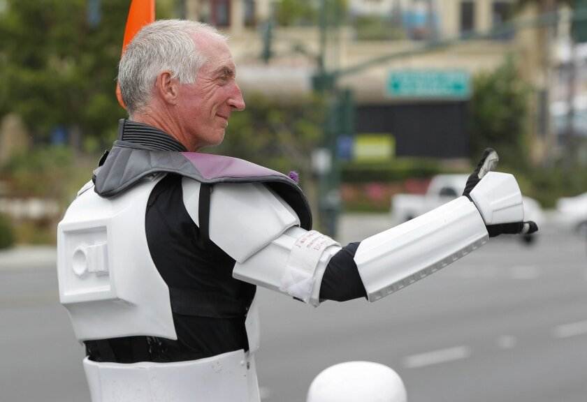 Kevin Doyle gives a thumbs up to people as he walks along Highway 101 in Leucadia.