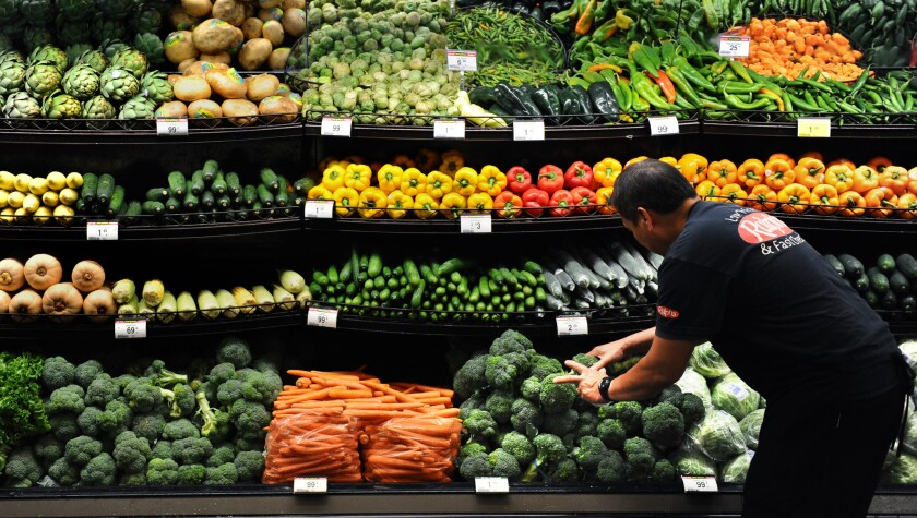 Produce clerk Frank Duenas arranges vegetables at the Ralph's grocery store in downtown L.A. Food prices are a key factor in the federal government's inflation calculations.