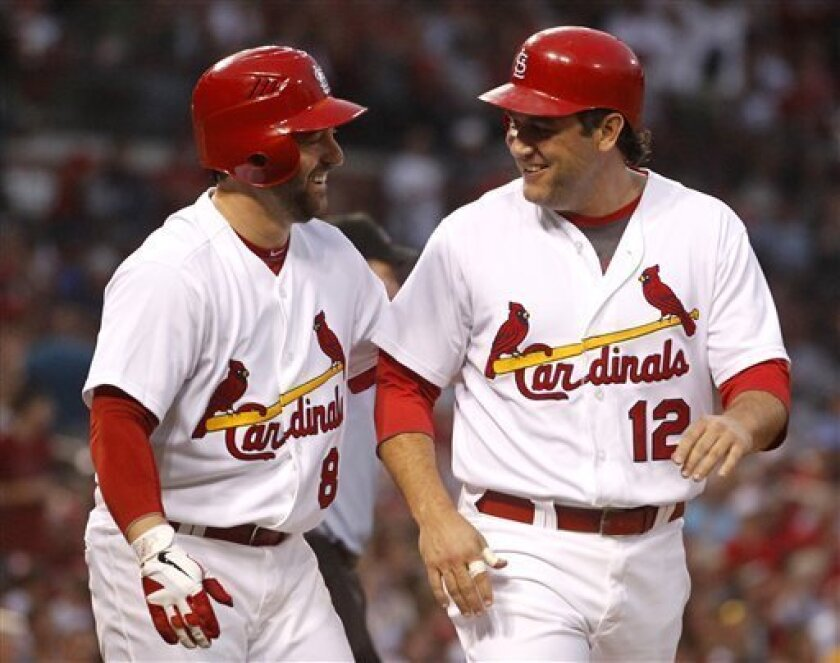 St. Louis Cardinals' Lance Berkman, right, is congratulated by teammate Nick Punto after scoring on a single by Yadier Molina during the third inning of a baseball game against the Atlanta Braves, Saturday, Sept. 10, 2011, in St. Louis. (AP Photo/Jeff Roberson)