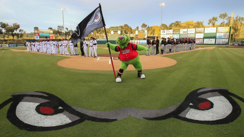 The Lake Elsinore Storm mascot stands next to home plate as Storm players and Modesto Nuts players line up on opening night at The Diamond in Lake Elsinore on April 6, 2017.