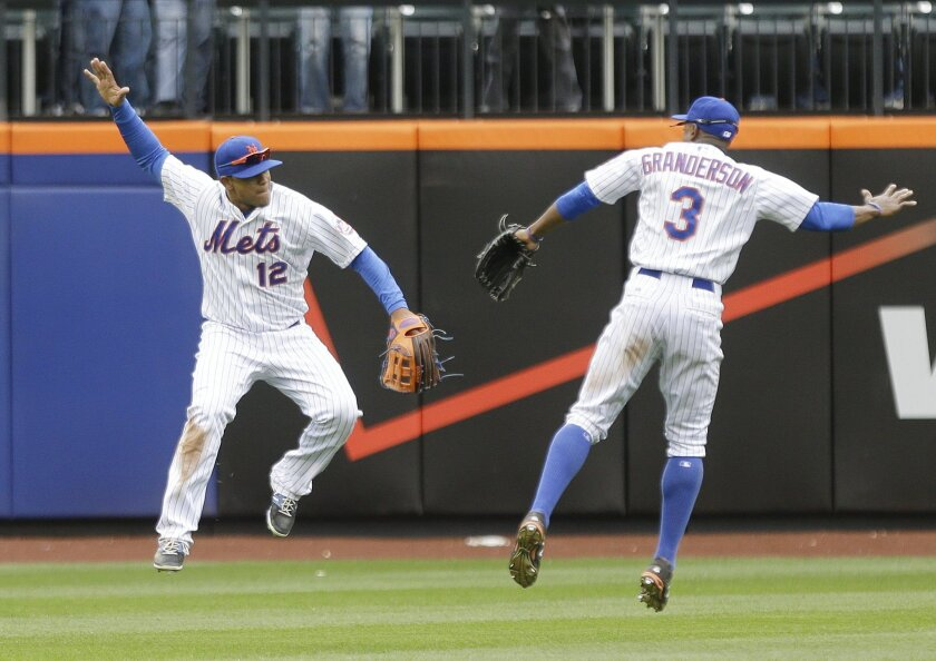 New York Mets' Juan Lagares (12) and Curtis Granderson (3) celebrate after their 6-3 win over the Atlanta Braves in a baseball game Thursday, April 23, 2015, in New York. (AP Photo/Frank Franklin II)