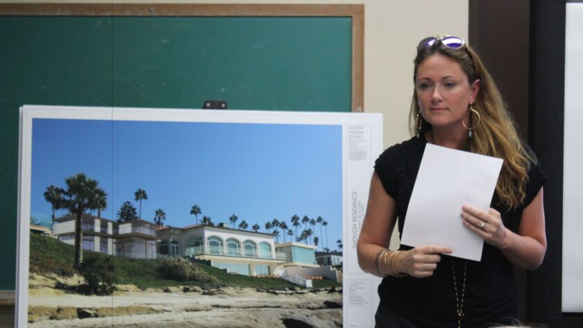 Architect Lauren Williams with a rendering of the proposed eco-friendly home on Camino de la Costa, as viewed from WindanSea beach.