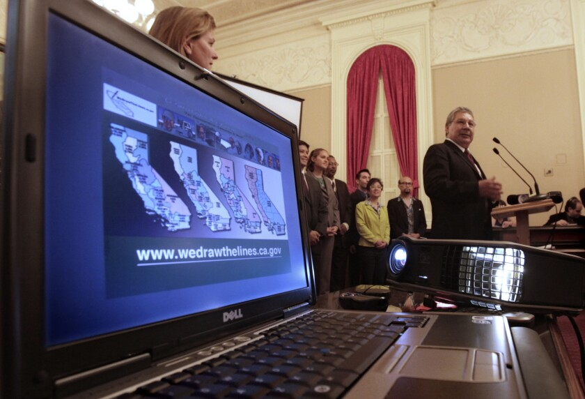 A California redistricting commission member discusses redistricting maps on a laptop screen at a Sacramento news conference