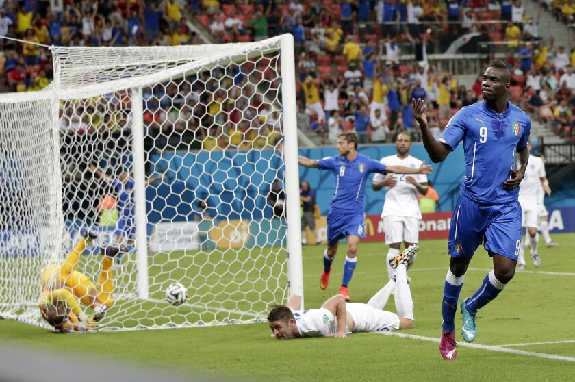 """FILE - In this Saturday, June 14, 2014 file photo, Italy's Mario Balotelli celebrates after scoring past England's goalkeeper Joe Hart, left, during the group D World Cup soccer match between England and Italy at the Arena da Amazonia in Manaus, Brazil. Pirlo's """"Panenka,"""" Schillaci's Golden Boot clincher and another emotional goal celebration from Marco Tardelli. The major-tournament rivalry between Italy and England has been marked by a few stand-out moments and they all belong to the Italians. England might have home advantage in the Euro 2020 final between the teams at Wembley Stadium on Sunday, July 11, 2021 but Italy has the edge historically. (AP Photo/Marcio Jose Sanchez, file)"""