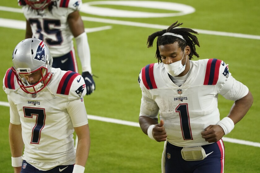 New England Patriots quarterback Cam Newton (1) runs off the field next to Jake Bailey (7) after a loss to the Los Angeles Rams during an NFL football game Thursday, Dec. 10, 2020, in Inglewood, Calif. (AP Photo/Ashley Landis)