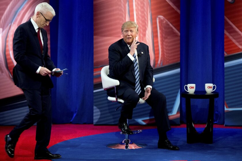 Republican presidential candidate Donald Trump, accompanied by Anderson Cooper, left, speaks with members of the audience during a commercial break at a CNN town hall at the University of South Carolina in Columbia, S.C., Thursday, Feb. 18, 2016. (AP Photo/Andrew Harnik)
