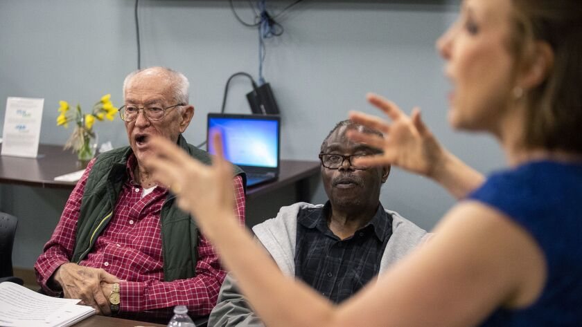 Parkinson's disease patients Mark Curley, left, and Samuel Sebabi work on their speech during a ther