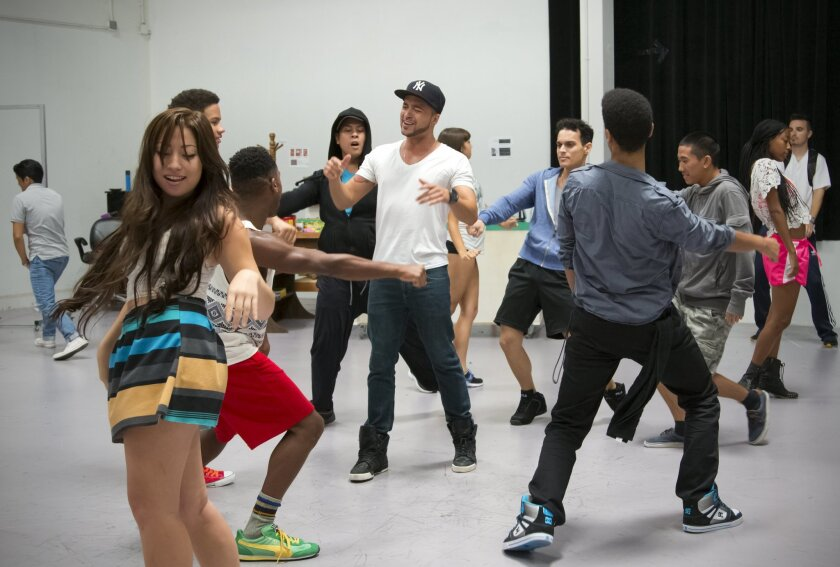 """Jai Rodriguez (center) and cast members rehearse a number from the San Diego Rep production of the musical """"In the Heights."""""""