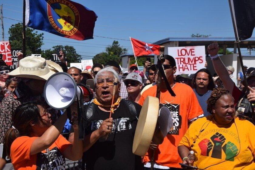 El doctor Cornel Pewewardy toca un tambor y encabeza una protesta mientras marchan por la avenida Nortwest Osmun y Sheridan Road hasta los accesos de Fort Sill, en protesta contra los planes del gobierno de Estados Unidos de mantener detenidos a menores migrantes en esa instalación, en Lawton, Oklahoma.