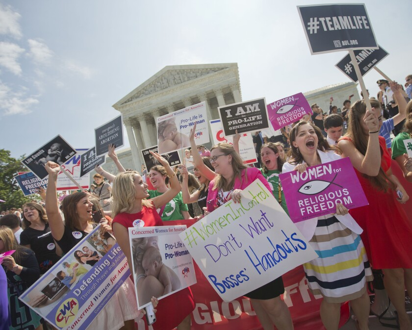 Demonstrators react to hearing the Supreme Court's decision on the Hobby Lobby case outside the court in Washington.