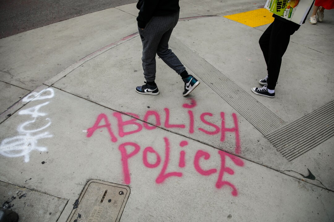 """The words """"Abolish Police"""" spray-painted on the sidewalk  in downtown Los Angeles."""