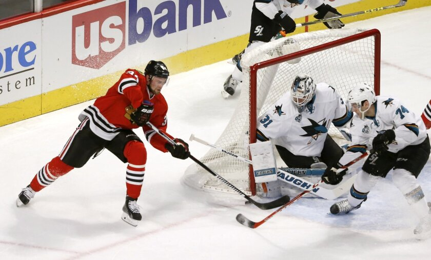 San Jose Sharks goalie Martin Jones (31) makes a save on a shot by Chicago Blackhawks defenseman Michal Rozsival (32) as Dylan DeMelo also defends during the first period of an NHL hockey game Tuesday, Feb. 9, 2016, in Chicago. (AP Photo/Charles Rex Arbogast)