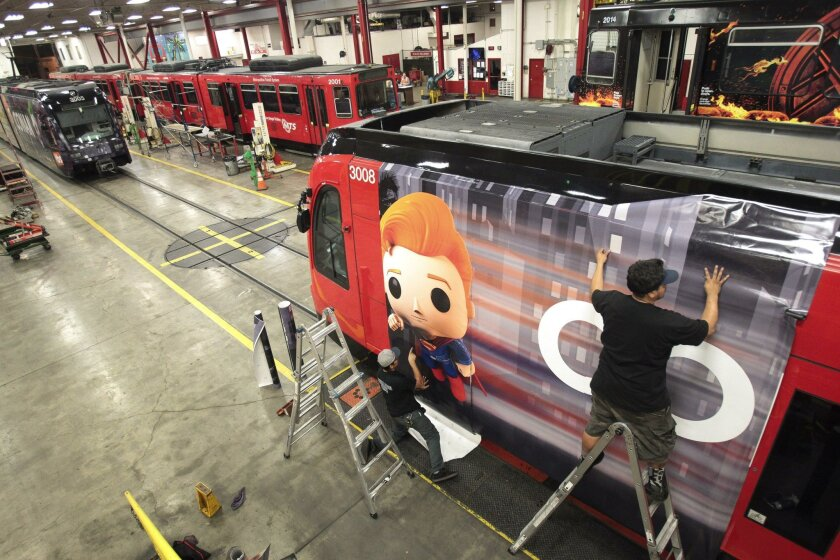 David Garcia, right, and Anthony Soltero put advertising wrap on an MTS trolley for TBS television host Conan O'Brien's talk show in preparation for Comic-Con next month.