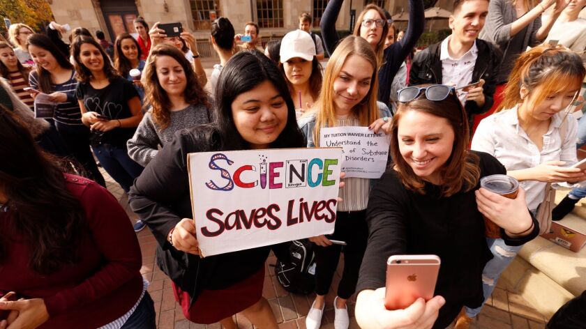 USC graduate students Mariel Bello, Nina Christie and Alyssa Morris, left to right, pose for a selfie to post online and forward to their congressman as they joined national protests against the GOP tax bill, which they say will significantly boost their taxes.