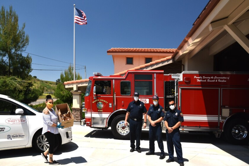 """The Foundation for Senior Care based in Fallbrook brought lunch to fire fighters at stations in the North County Fire Protection District as a """"thank you"""" to first responders who serve the senior community in the Fallbrook/Rainbow/Bonsall area. Maria Fajardo and others from the Foundation delivered the free lunches prepared by Major Market and donated by the Foundation Just before her delivery, three paramedics (Edgar Guzman, Rafael Gonzalez and Anthony Nissan) responded to a call. From left Maria Fajardo bringing lunch to firefighters Bruce Moore, Mathew Anderson and Captain Richard Berry of North County Fire Protection District (NCFPD) Station #5."""