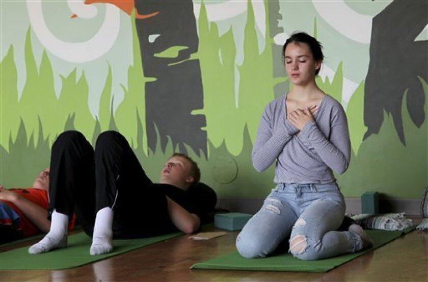 Nora Pearson, derecha, practica concentración en la respiración durante la clase de atención plena en la secundaria Wilson en Portland, Oregon. El curso de un año forma parte de una serie de programas que están incorporando concentración, yoga y meditación a las escuelas para darle beneficios socioemocionales a los estudiantes.