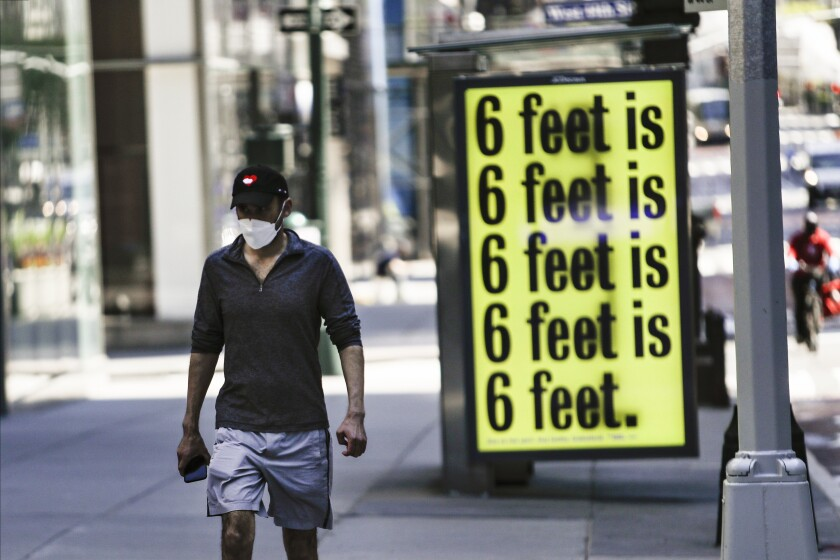 A pedestrian walks past a social distancing reminder in New York.