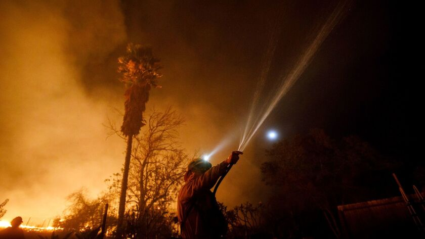 A firefighter uses a garden hose to spray water on rooftop embers while working to save a home on Vi