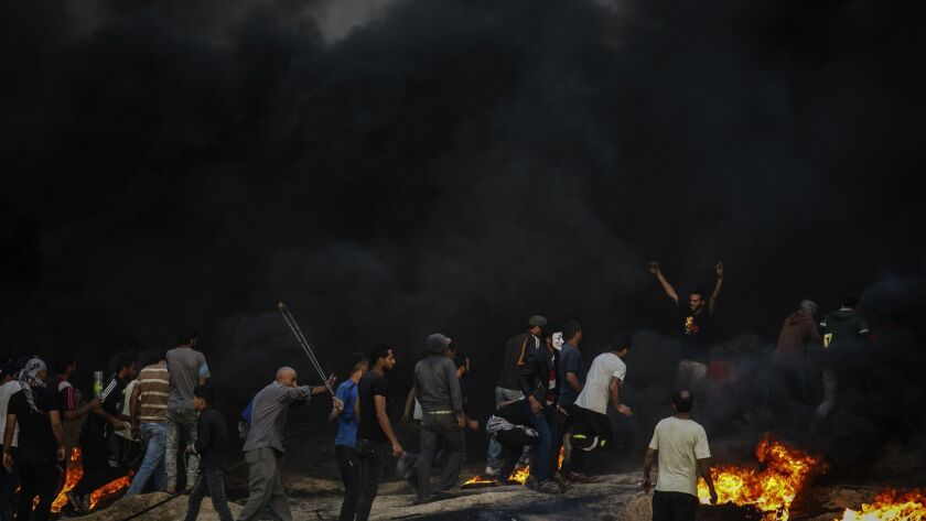 DEIR AL-BALA, GAZA -- TUESDAY, MAY 15, 2018: Protesters make their way into the black smoke during a