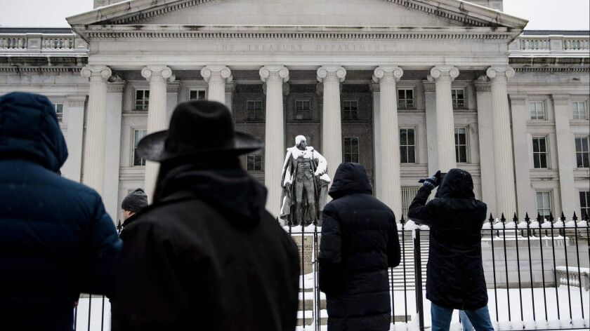 People walk past the Treasury Department building in Washington on Jan. 13.