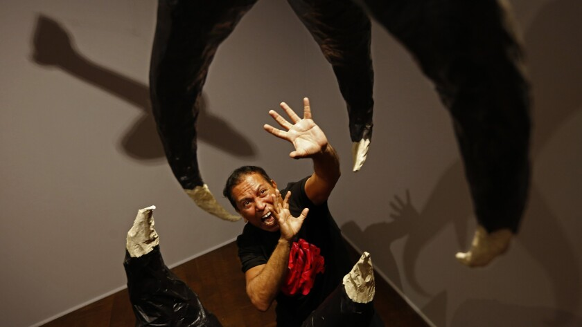 """Gronk poses with his sculpture in honor of """"The Giant Claw"""" at the Craft & Folk Art Museum."""