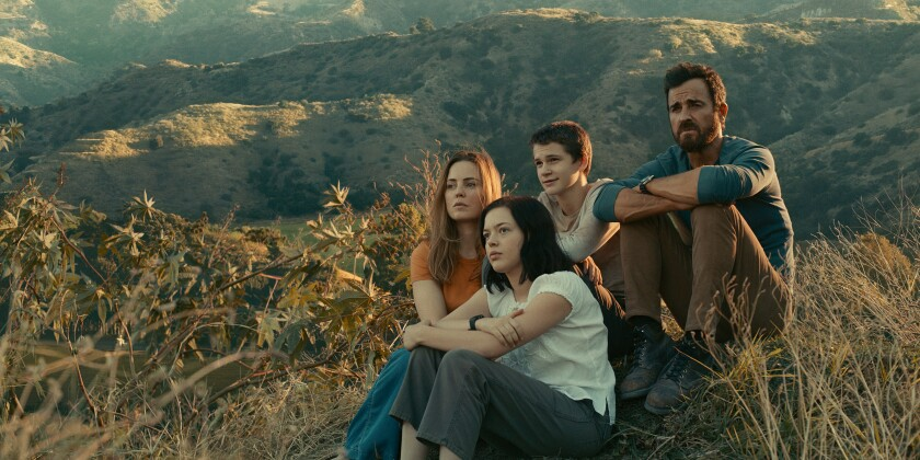 A family of four sits on a ridge in a remote mountain range