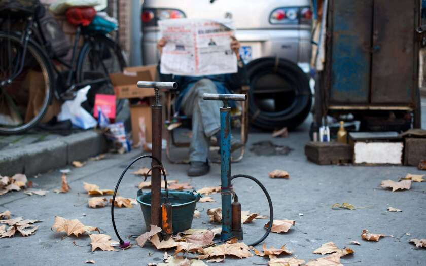 A man who repairs bike tires reads a newspaper behind his air pumps in Shanghai on Nov. 27, 2014. China's media regulator has issued an order restricting puns and wordplay in copy.