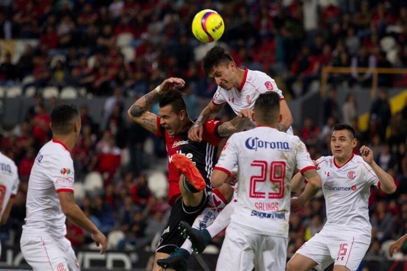 El jugador de Atlas Milton Caraglio (i) y Aldo Benitez (d) de Toluca pelean por un balón este viernes 19 de enero de 2018, durante el juego correspondiente a la jornada 3 del torneo mexicano de fútbol celebrado en el estadio Jalisco en la Ciudad de Guadalajara (México). EFE