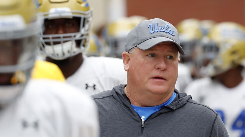 UCLA coach Chip Kelly leads his players onto the field.