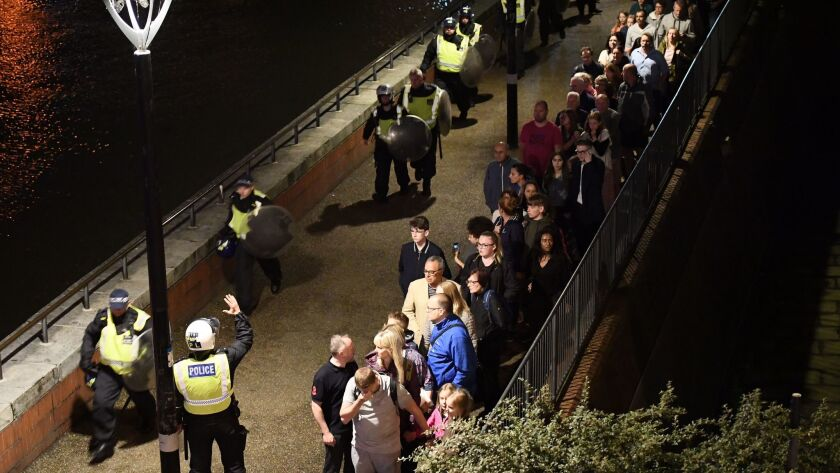 People are led to safety away from London Bridge shortly after police responded to reports of a van plowing into people on June 3.