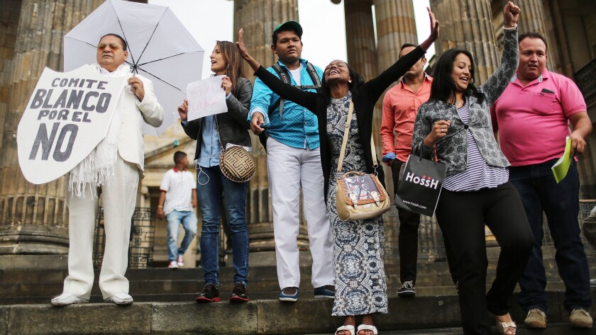 """A man advocating against the FARC peace referendum, left, stands with """"yes"""" vote supporters in front of Congress on Sept. 28, 2016, in Bogota, Colombia."""