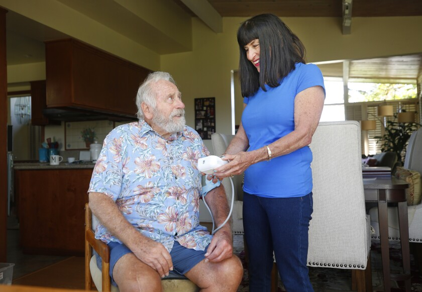 Mary Ellen Gross takes the blood pressure of her husband, Ted, using the Glennercare app, which supports dementia patients and caregivers through daily check-ins.