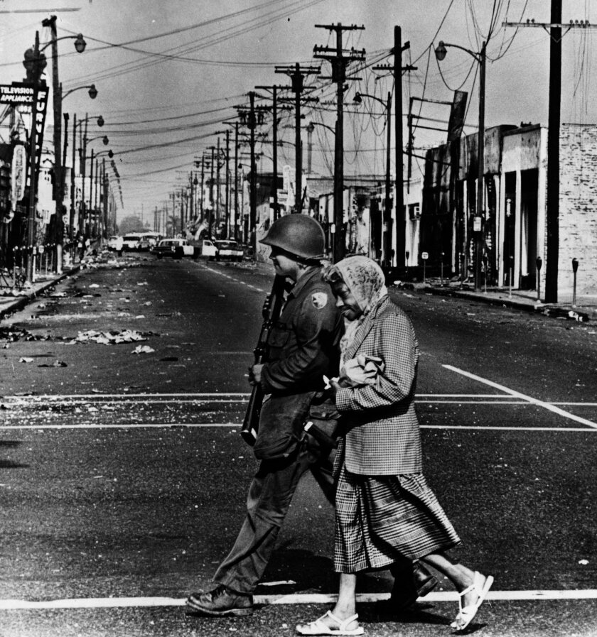 A National Guardsman escorts a Watts resident across rubble-strewn Wilmington Avenue after rioting in 1965.