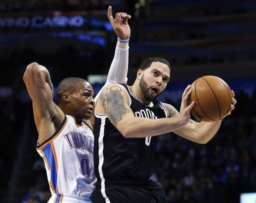 Brooklyn Nets guard Deron Williams, right, shoots in front of Oklahoma City Thunder guard Russell Westbrook (0) in the first quarter of an NBA basketball game in Oklahoma City, Wednesday, Jan. 2, 2013. (AP Photo/Sue Ogrocki)