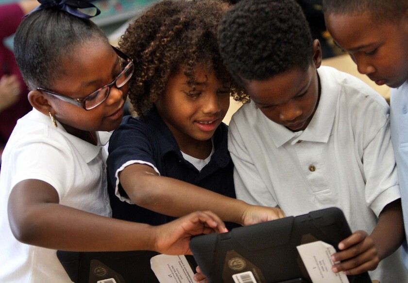 L.A. Unified students explore their new iPads in this photo from the fall of 2013.