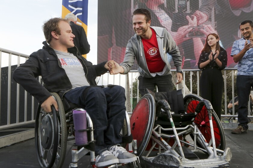 Patrick Ivison, left, shakes hands with Zak Williams, who presented him with a rugby wheelchair from the Challenged Athletes Foundation. Williams' siblings, Zelda and Cody, are behind him. The children of the late Robin Williams are ardent supporters of the foundation.