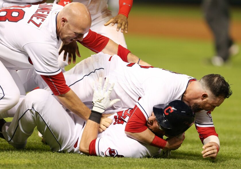 Cleveland Indians' Yan Gomes, bottom, is tackled by Jason Kipnis and Chris Gimenez, left, after hitting a single to score the winning run against the Texas Rangers during the 11thinning of a baseball game Wednesday, June 1, 2016, in Cleveland. The Indians won 5-4. (AP Photo/Ron Schwane)