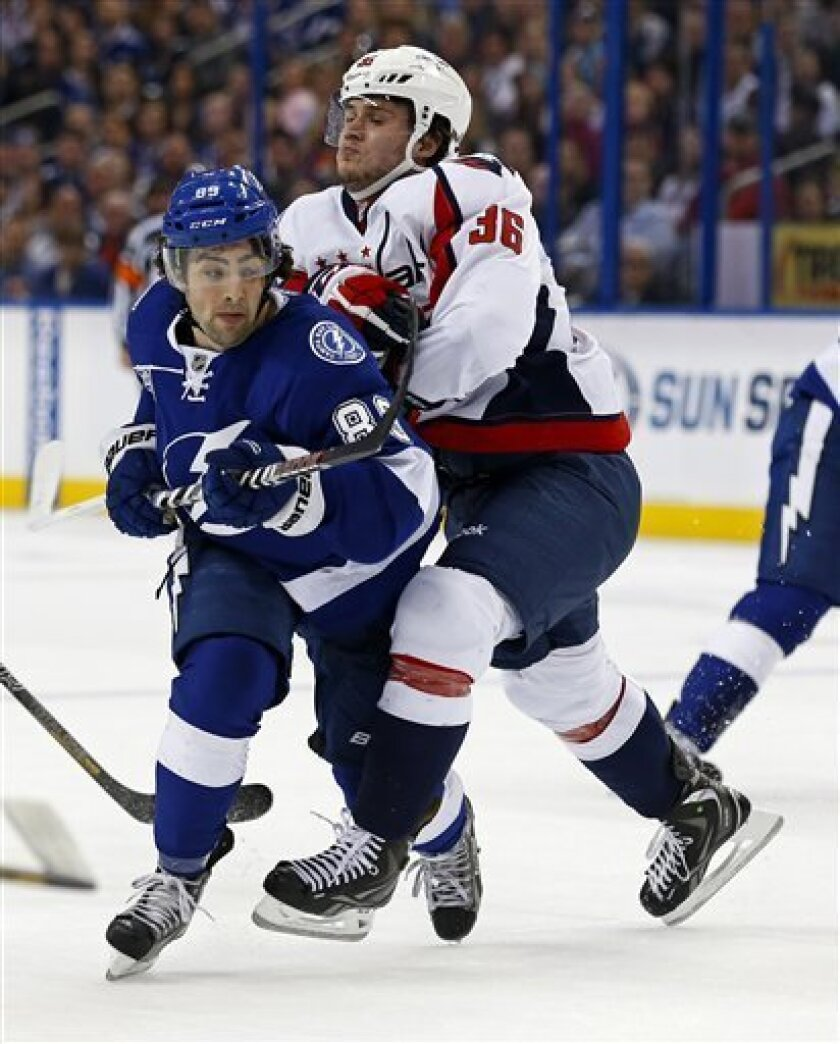 Tampa Bay Lightning's Cory Conacher, left, is checked by Washington Capitals' Tomas Kundratek during the second period of an NHL hockey game on Thursday, Feb. 14, 2013, in Tampa, Fla. (AP Photo/Mike Carlson)