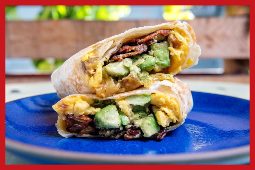 A cut-open and stacked breakfast burrito on a blue plate.