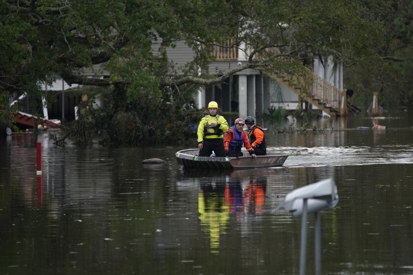 Animal rescue drive a boat down a flooded street in the aftermath of Hurricane Ida, Wednesday, Sept. 1, 2021, in Lafitte, La. Following Hurricane Ida, mutual aid networks sprang into action to supplement the more established relief services from federal and local governments, and charities. (AP Photo/John Locher)