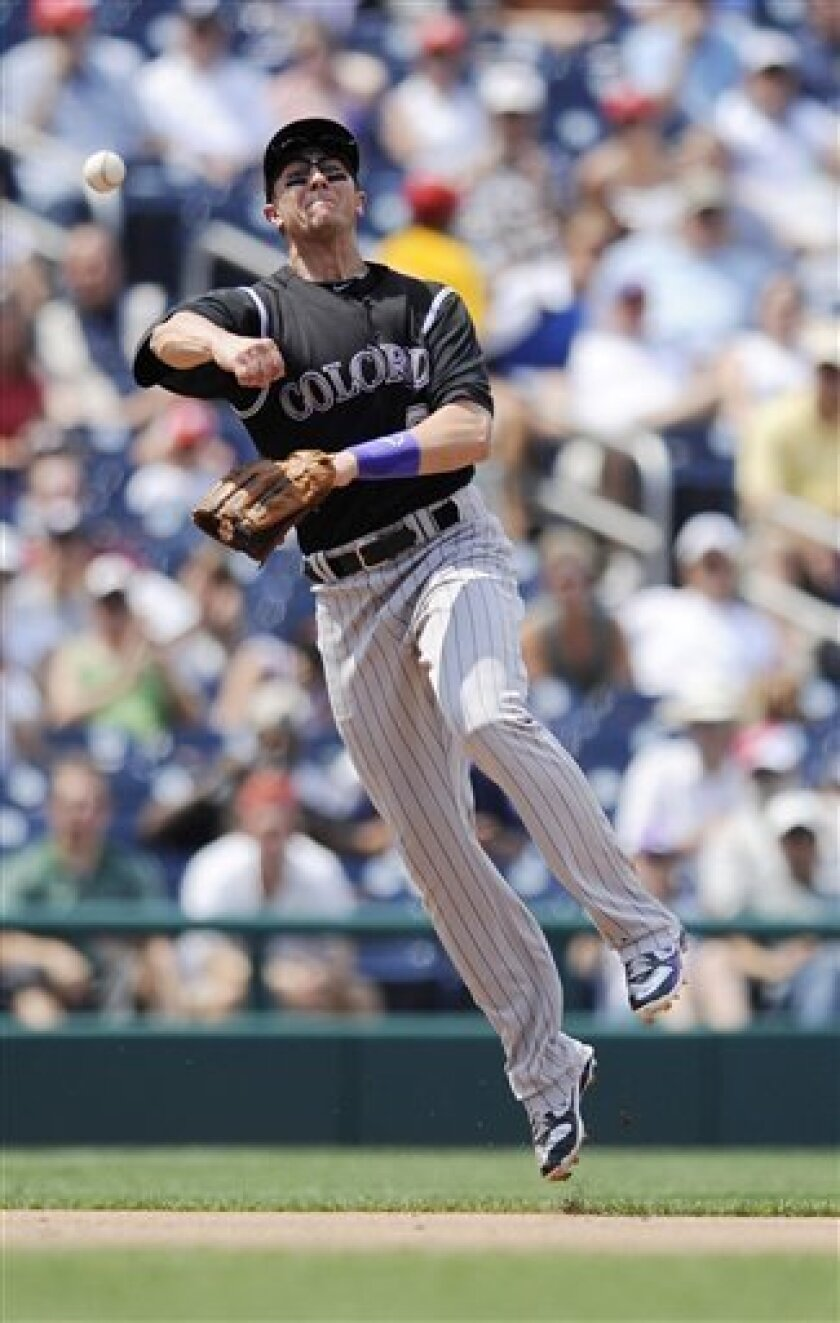 Colorado Rockies shortstop Troy Tulowitzki throws the ball to first but is unable to get Washington Nationals' Ian Desmond, who was safe with a single, during the sixth inning of a baseball game, Sunday, July 10, 2011, in Washington. The Nationals won 2-0. (AP Photo/Nick Wass)
