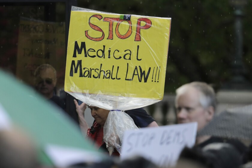 A protester holds a misspelled sign opposing medical martial law.
