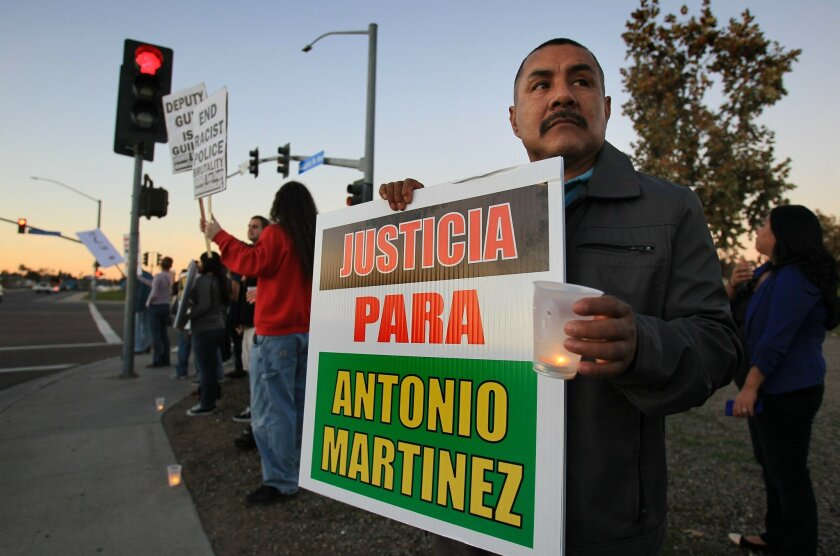 Francisco Martinez, father of beating victim Antonio Martinez, 21, holds a candle and sign demanding justice for his son during a dusk protest against sheriff's brutality in Vista.