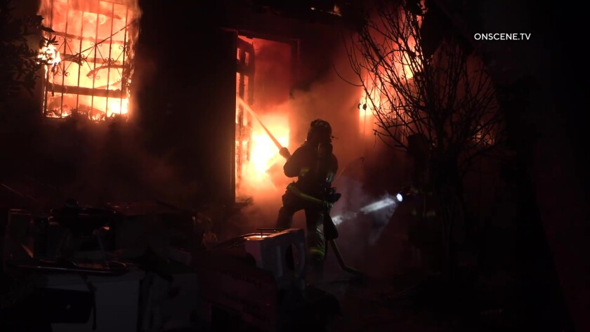 Firefighter sprays water inside a burning home