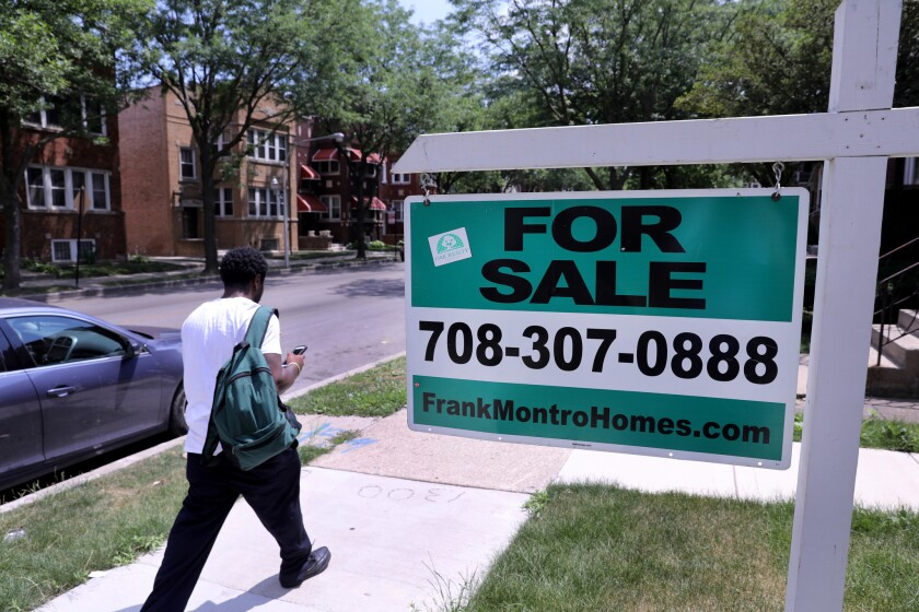 """A """"for sale"""" sign stands in the yard of a single-family home in Chicago's Austin neighborhood on the West Side on July 6, 2017. July home sales in the Chicago area fell 4.9 percent from the previous year, continuing a trend of weaker sales that began in the spring, according to data released Aug. 24 by Illinois Realtors."""